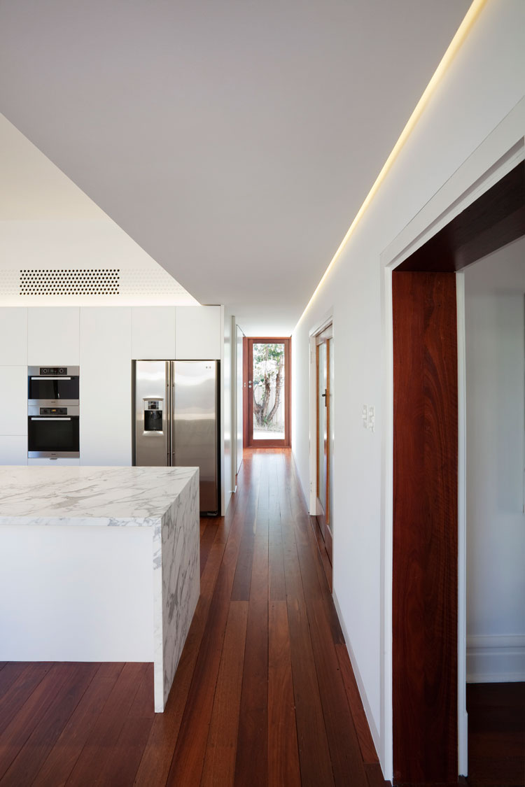 A door at the end of the new living room carefully frames the view of a tree beyond at Westbury Crescent Residence