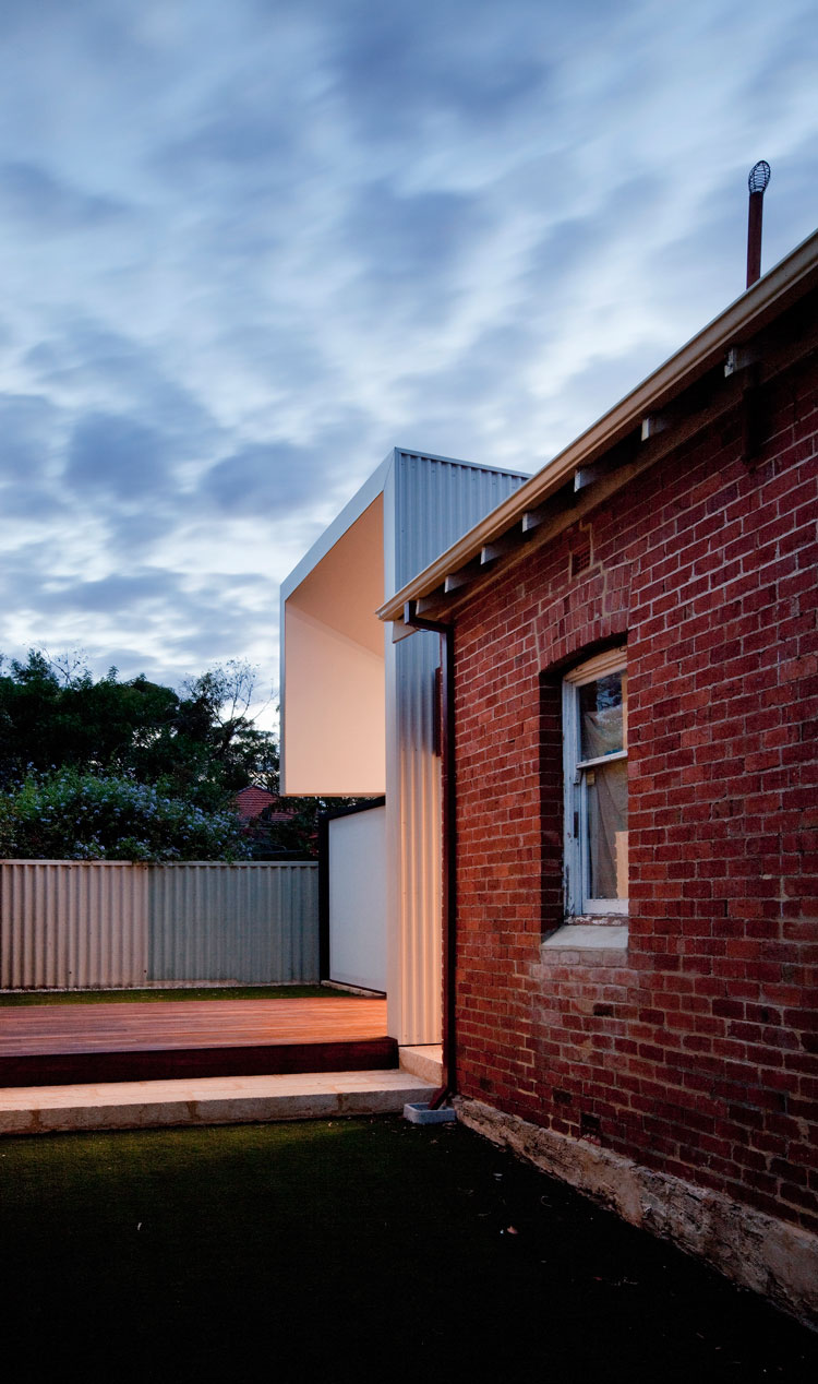The connection between old and new at Westbury Crescent Residence is marked by a strong contrast between the heavy, solid materiality of the existing Federation home and the lighter modern look of the corrugated iron