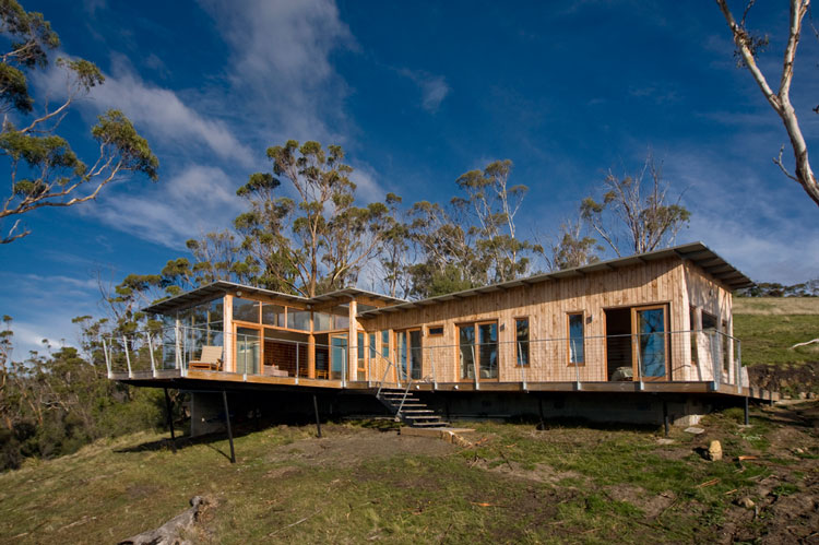 Bruny Shore House is made from timber and hangs over a slope towards the ocean at Bull Bay in Tasmania