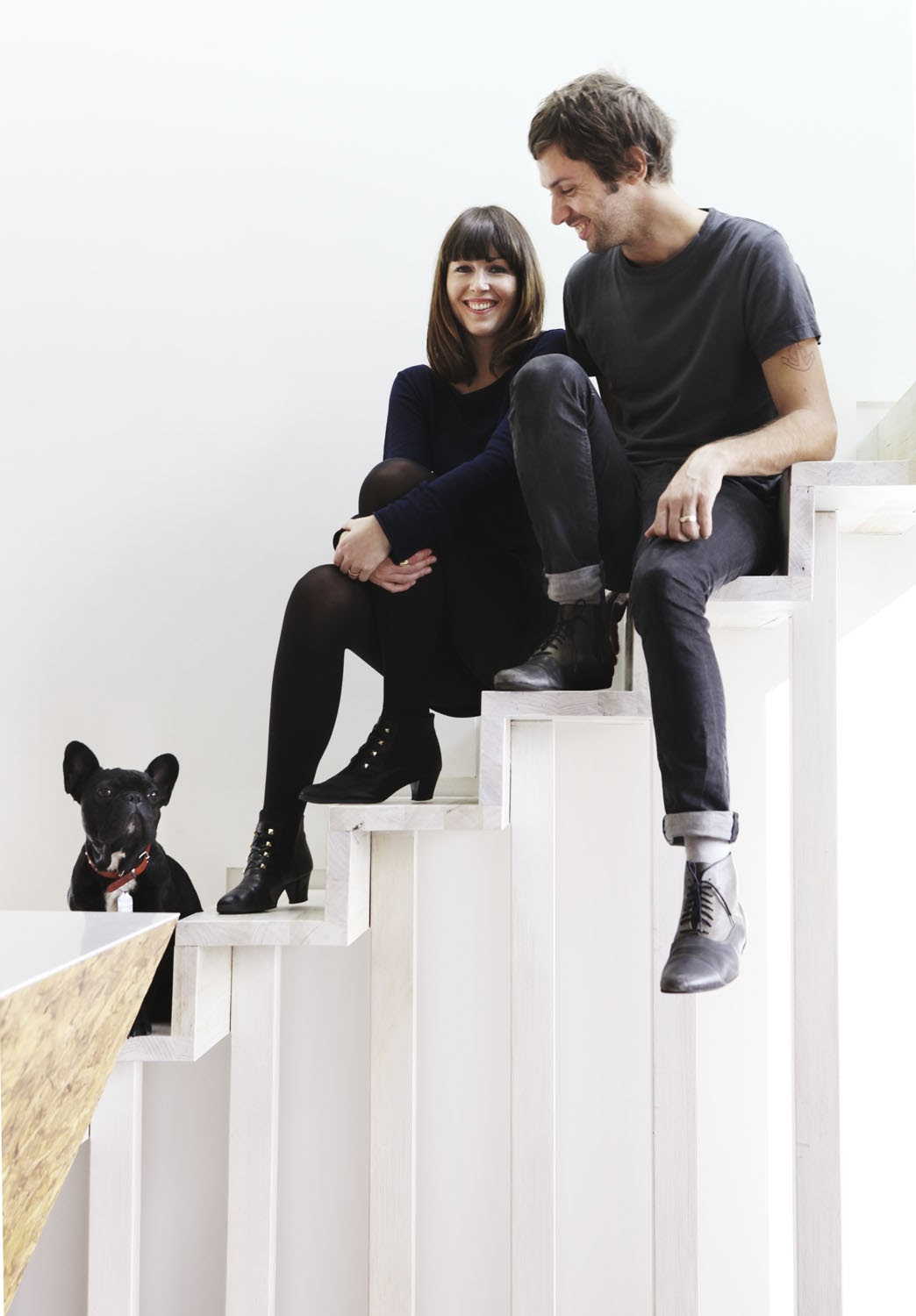 Ben Edwards, his partner and their pet dog sit on the stairs of their home Cubby House