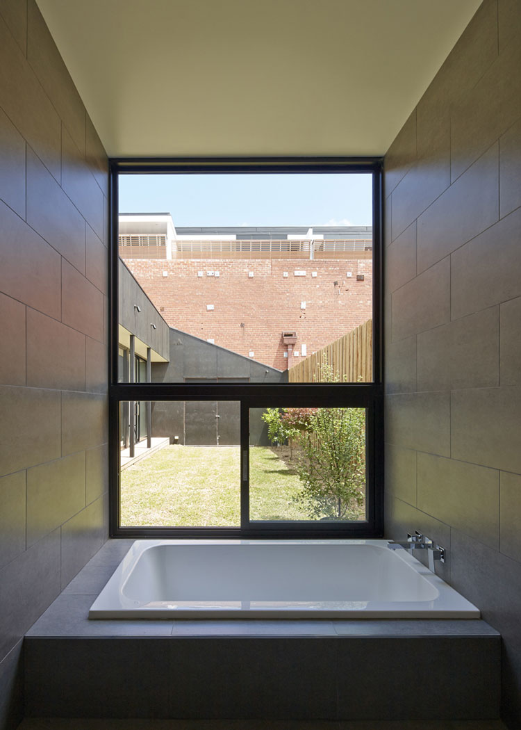 Engawa House bathroom overlooks lawn area and red brick warehouse