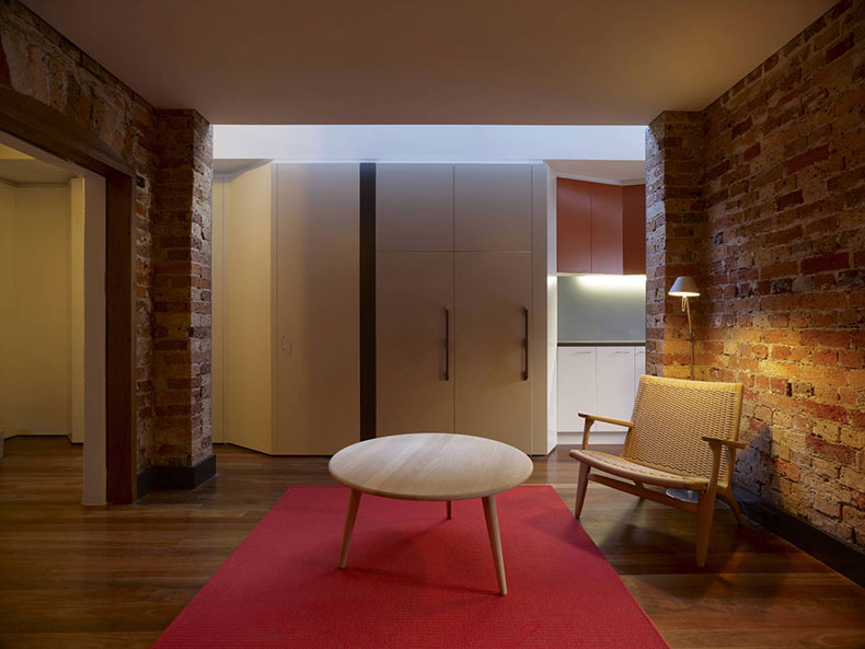 Fitzroy Terrace in Sydney's lounge area feels warm with reds and the original brickwork and details
