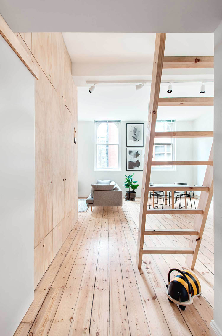 Flinders Lane Space Efficient Apartment open plan living area steps lead to an upstairs mezzanine for guests