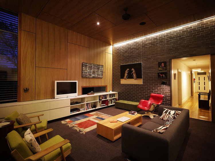 Haberfield House living area at night has dramatic lighting for glazed brick wall