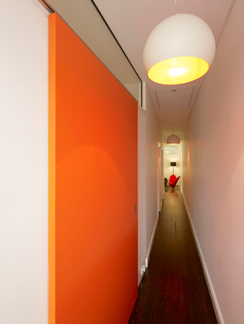 A long corridor runs past the bedroom in the existing part of the home, leading to the new living areas