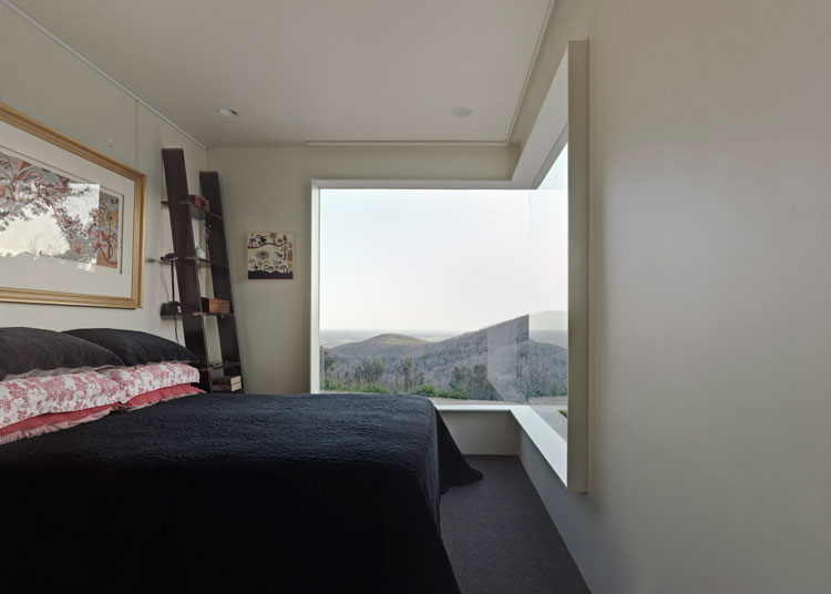 Frameless corner windows at Hillside Habitat make the walls disappear into the surroundings