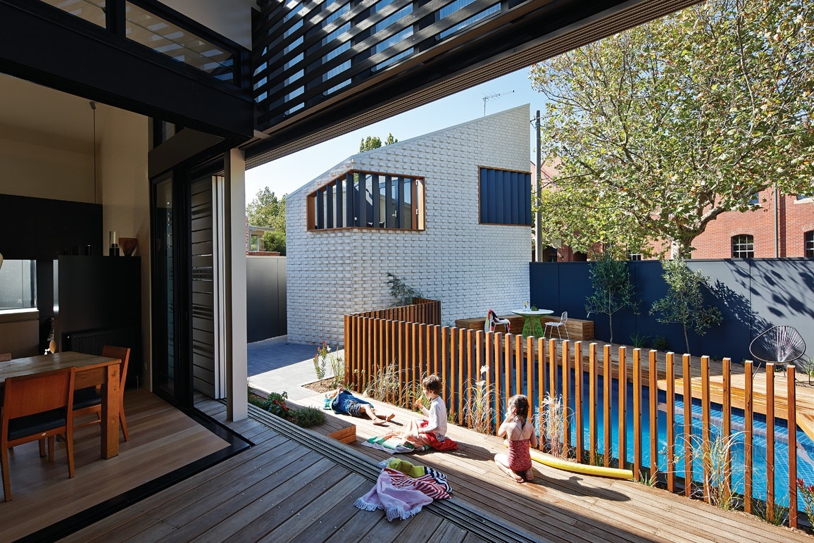 Children play around the pool on new decking area in the project House Reduction