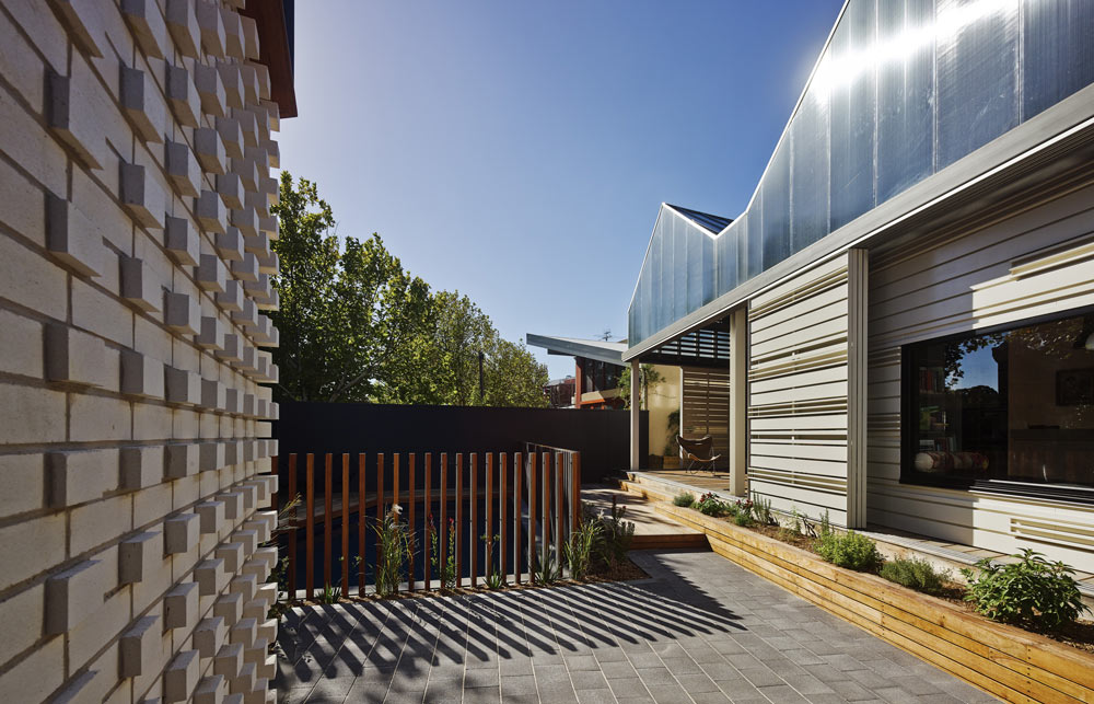 The polycarbonate facade shimmers during the day adding to other rich textural materials like the textured brick facade