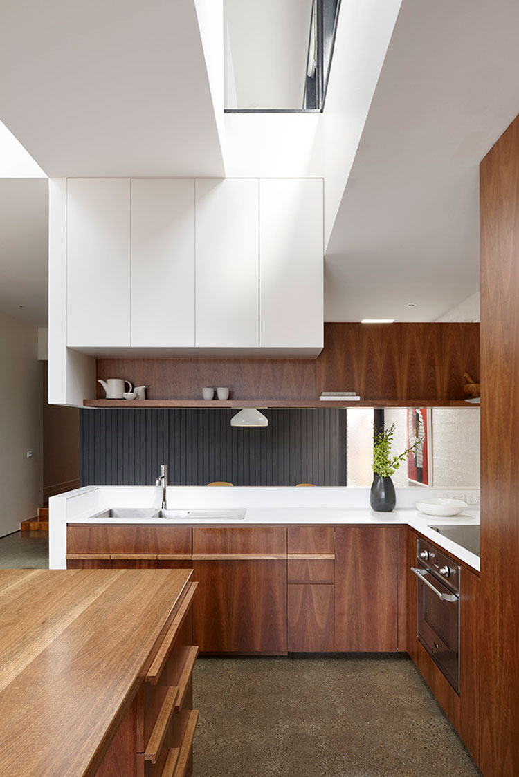 North Fitzroy House kitchen uses timber veneer and a textured white panel it's richly textured
