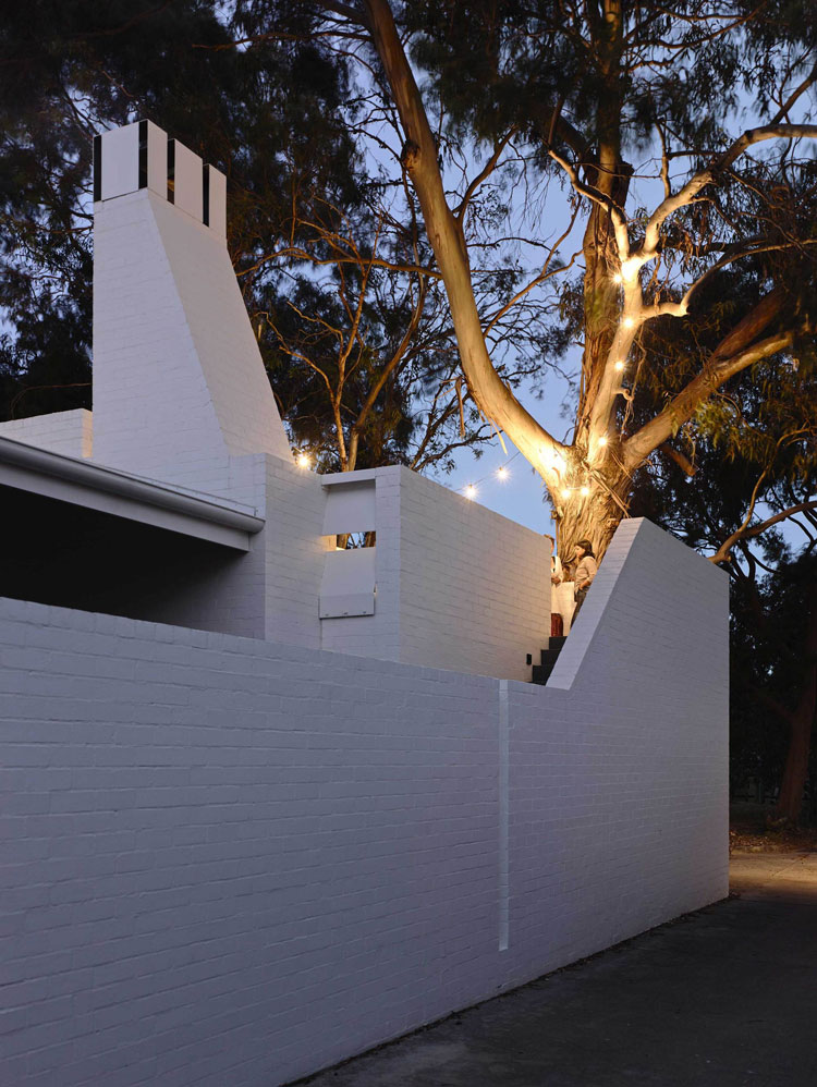 Lights in the eucalyptus tree light up the upstairs terrace in Park Lane House