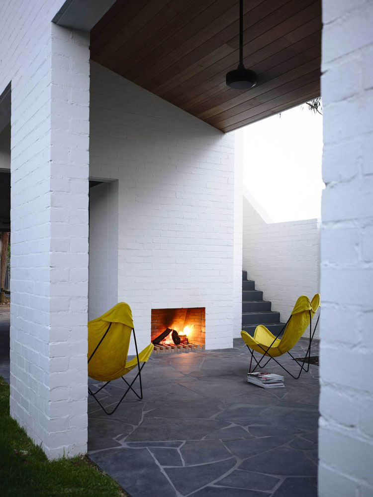 A covered external courtyard is warmed by a fireplace