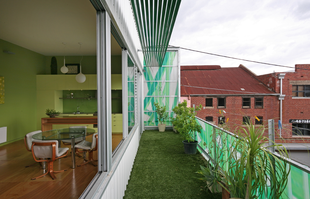 A view of Polygreen's artificial turfed deck overlooking neighboring red brick warehouses in an industrial lane in Northcote