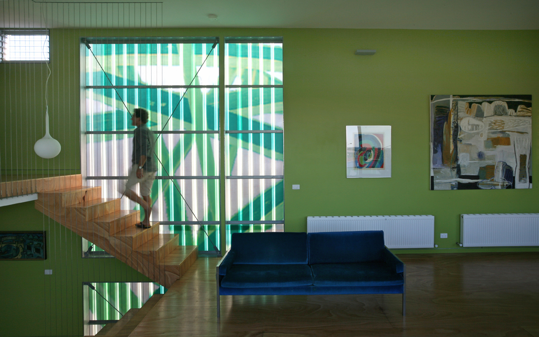 Michael Bellemo walks up the stairs in his home Polygreen with translucent fiberglass and spray painted pattern behind