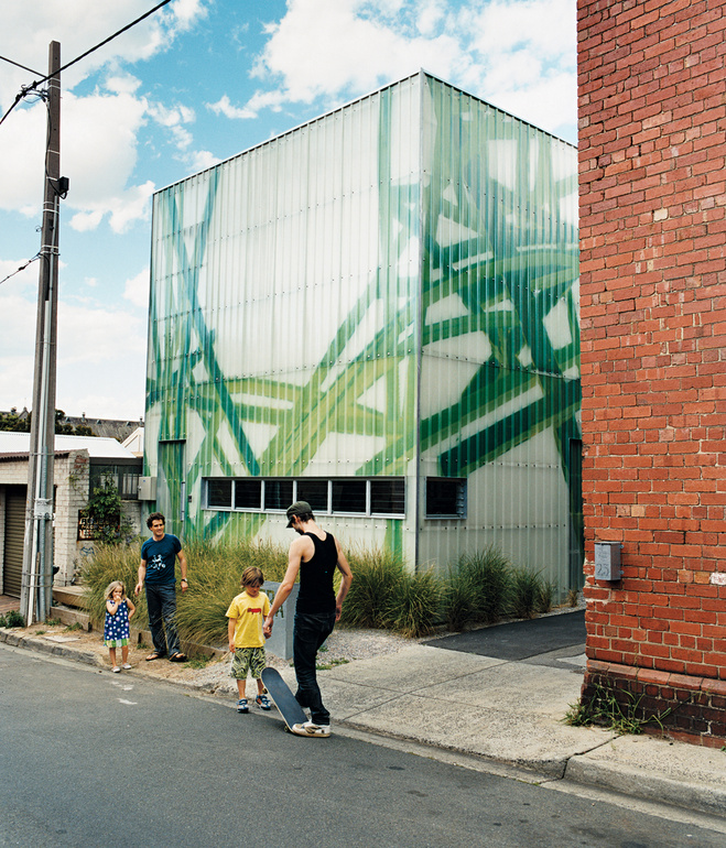 Michael Bellemo, his children and a friend play outside their modern spray painted home, Polygreen