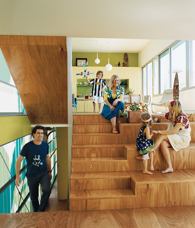 Michel Bellemo, Cat Macleod and their family sit on their amphitheater style stairs in their home Polygreen