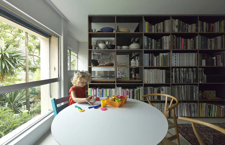 Potts Point Apartment dining area receives light from a nearby window, and is separated from the kitchen by a full height bookshelf