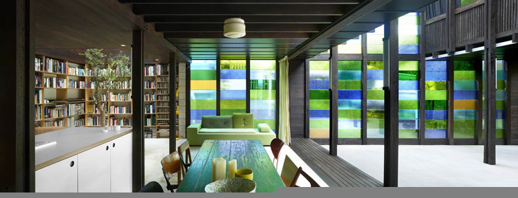 Dazzling greens, blues and ambers inject beautiful colored light into the living area at Raven Street House