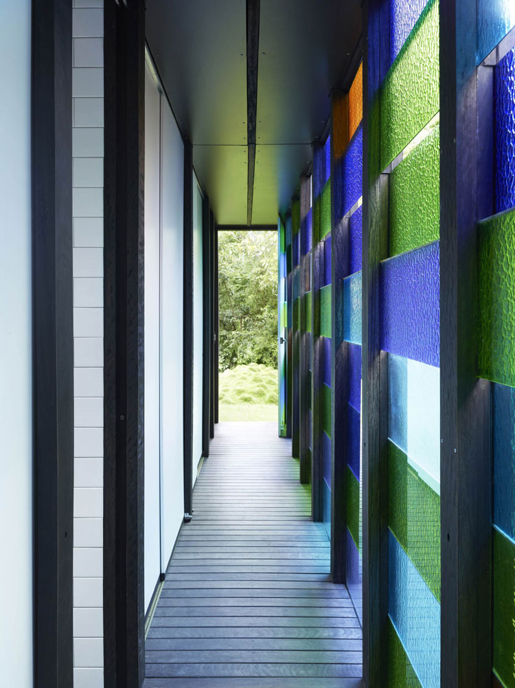 A hallway and storage area at Raven Street House is lit by varying colored panes of glass