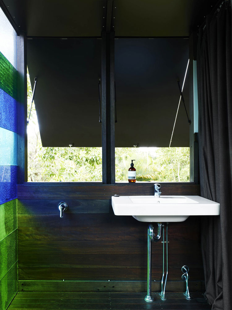 The shower room off the master bedroom is simple with dark timbers, highly saturated colored glass and openable shutters