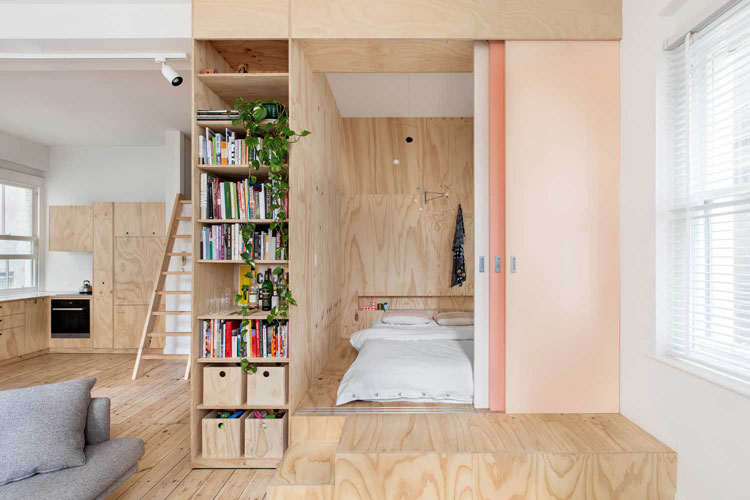 Flinders Lane Space Efficient Apartment bed is raised on a platform and separated from the living area by a Japanese-inspired screen