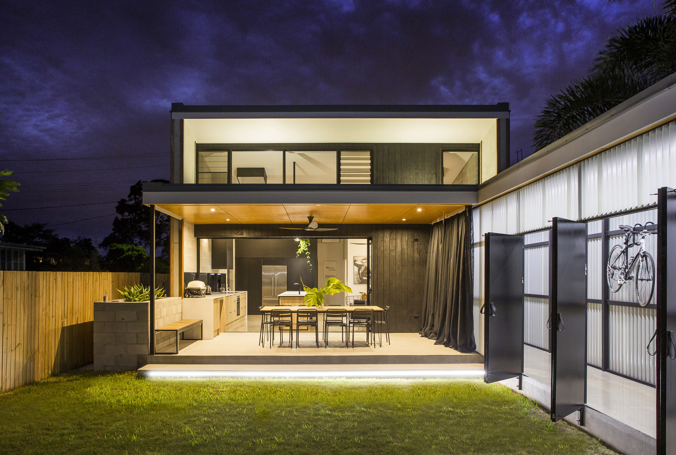 Covered outdoor dining spills onto a courtyard in this for Clerestory house designs