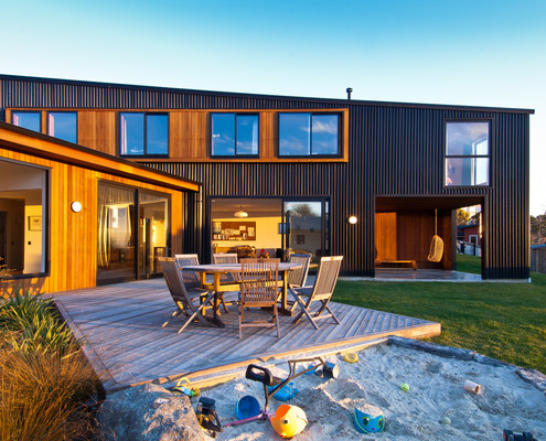 Warm nz house designed to embrace the sun and view of for Coastal home designs nz